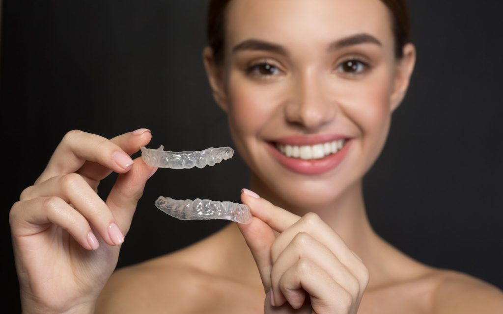 Woman holds up ClearCorrect aligners for top and bottom teeth