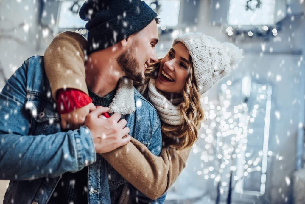 Couple in the snow smile at each other