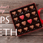 A box of chocolate hearts with a red ribbon in the shape of a heart next to it for Valentine's Day