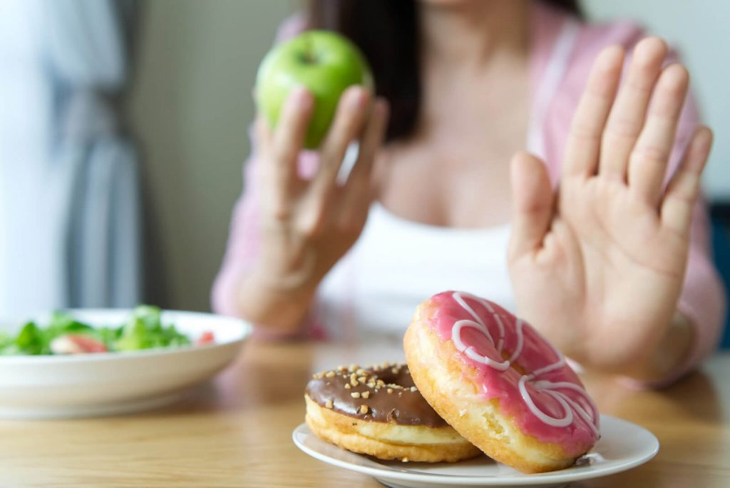A woman substitutes an apple and salad for doughnuts to have less sugar in her diet