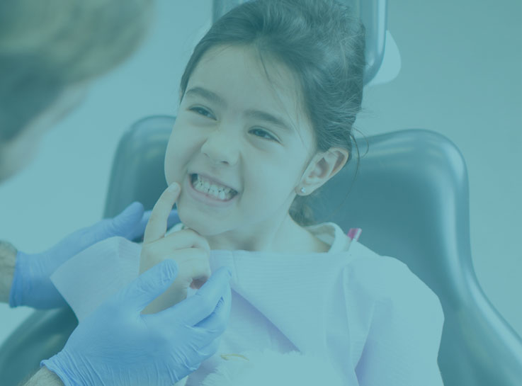 A young girl points at her mouth where a tooth hurts while she's in a dental chair at a dentist's office